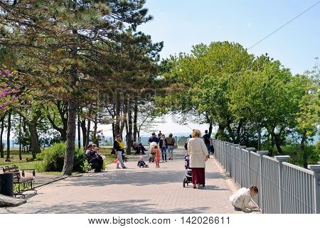 ANAPA, RUSSIA - MAY 02, 2016: Joyous residents and guests of resort town Anapa walk along seaside promenade in underpopulated spring warm sunny day