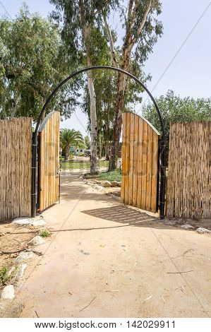 Wooden double gates in the reed fence the entrance to the camping in Israel