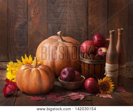 Autumn still life - pumpkins, autumn leaves and apples against the background of old wooden wall.