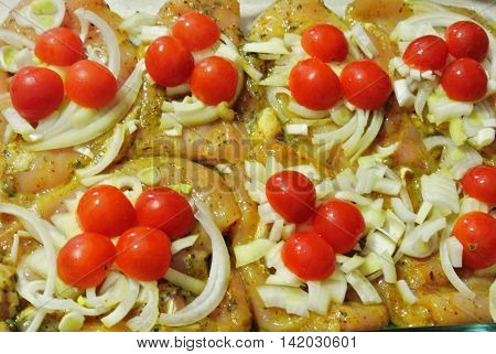 Raw chicken fillet marinated in spices and herbs with onions and cherry tomatoes, ready to be placed in oven