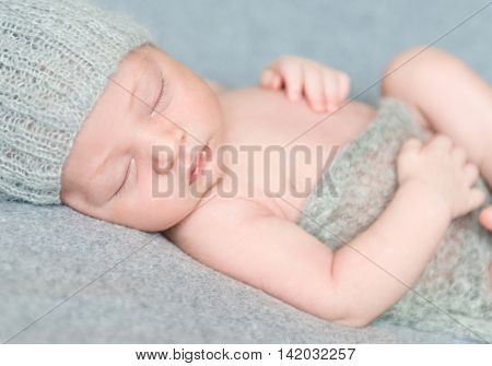 peacefully sleeping newborn baby in gray knitted hat covered with blanket, close-up