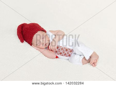 sleeping newborn baby in national ukrainian costume with embroidery and red hat