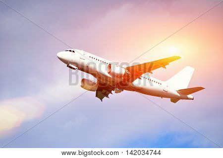 Airplane closeup.Travel background with airplane flying in the colorful sunset sky. White flying airplane. Airplane in the sunlight. Closeup of flying airplane with blank livery.Airplane in the flight