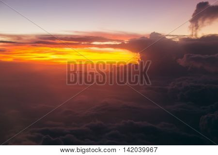 Photo of Lurid sky with clouds during sunrise. Air travel by plane. Soft focus