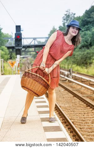 young woman in red dress and blue hat holding a basket and waiting on platform at train station