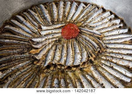 Cooked sardines and tomato in a pan