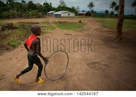 Mabendo Sierra Leone - May 31 2013: Mabendo small village in Sierra Leone Africa the lives of children playing happily with a wheel