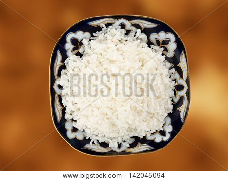 Beautiful dish with boiled rice on a gold background. View from above