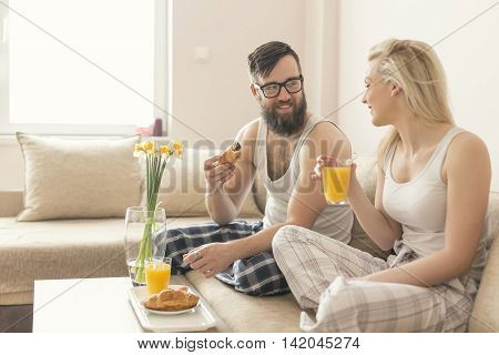 Couple in love sitting on the couch in the living room wearing pajamas after getting up in the morning enjoying the morning and having breakfast