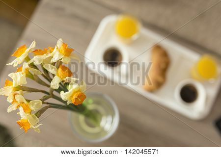 Top view of a breakfast tray on a table in a hotel room selective focus on one of the flowers in a vase next to a tray