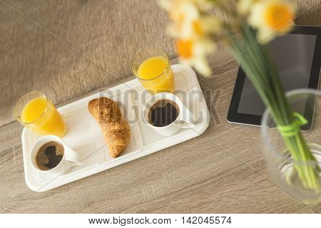 Top view of a breakfast tray on a table in a hotel room with tablet computer placed next to it