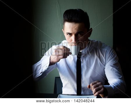 Man young handsome elegant model wears white shirt black skinny necktie sits at table drinks coffee and looks in camera indoor on grey background
