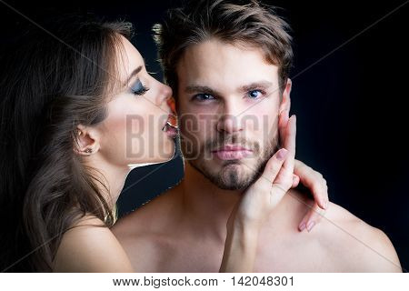 Closeup portrait of young beautiful sexual couple of brunette woman with long hair embracing and kissing handsome muscular man in studio on black background horizontal picture