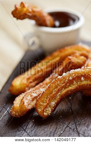 churros con chocolate, a typical Spanish sweet snack, on a rustic wooden table