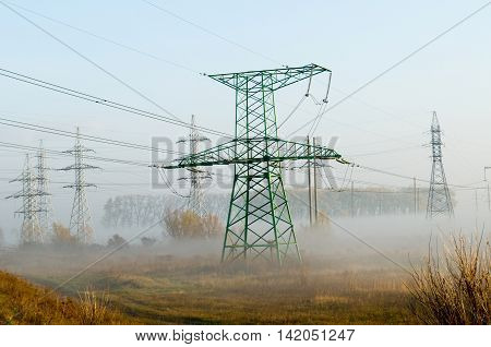 Electricity transmission lines are associated to autumn landscape. Industrial constructions are shrouded in morning mist.
