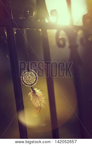 Handmade dream catcher hanging on an iron fence in sunset of a beautiful sunny day