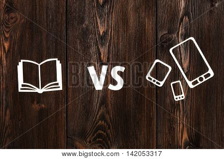 Book vs ebook or pad. Abstract paper conceptual image on wooden background