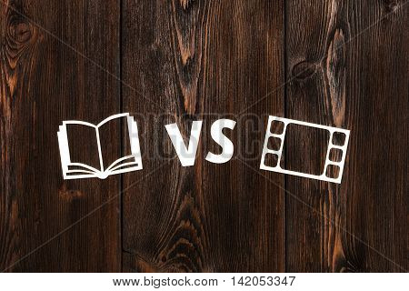 Reading book vs movie. Abstract paper conceptual image on wooden background