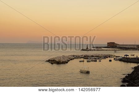 Harbour with boats in front of Capri in a summery sunset
