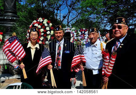 New York City - May 262014: Asian-American veterans with American flags at the Memorial Day ceremonies in Riverside Park *
