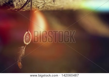 Handmade dream catcher hanging on a wooden fence in sunset of a beautiful sunny day