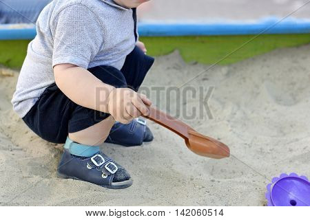 Kid playing on the Playground in the warm time of the year. The child digging in the children's sandbox.