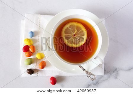 Cup of black tea with lemon and multicolored chocolate drops