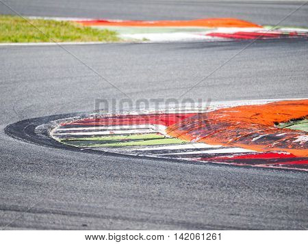 Close view of circuit corner curb with tyre's signs on asphalt perfect for motor sport concepts and background. Intentionally blurred.