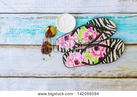 Beach Accessories. Summer Shoes And Towel With Sunglasses Wooden Background