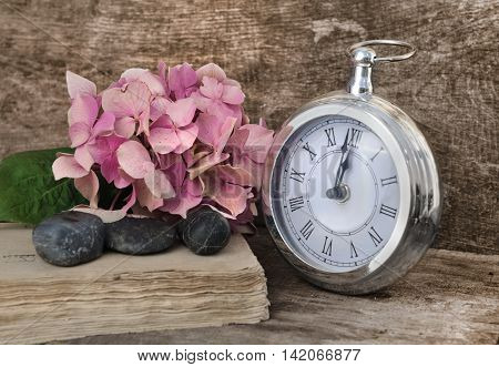 retro clock at twelve soon with flowers on old book on wooden background