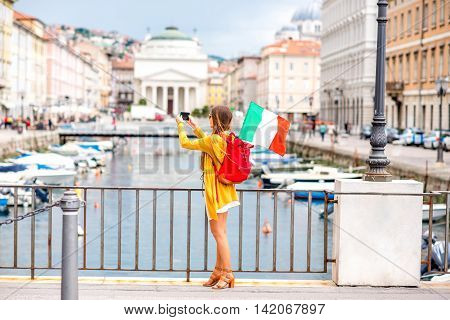 Young female traveler with backpack and italian flag photographing cityscape with phone in Trieste city. Traveling in Italy