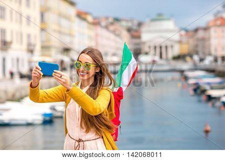 Young female traveler with backpack and italian flag making selfie photo with phone on Trieste city centre background. Traveling in Italy