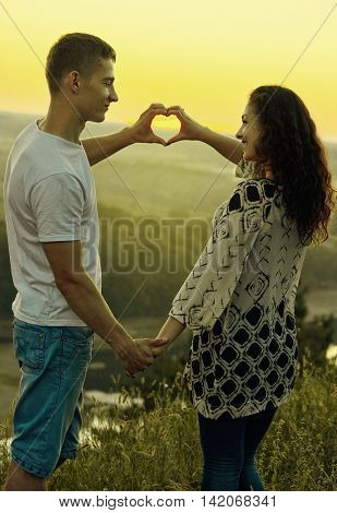 romantic couple at sunset make a heart shape from hands, beautiful landscape and evening sky, love tenderness concept, young adult people, yellow toned
