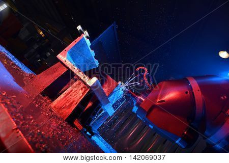 CNC drilling steel at work with water cooling blue red film