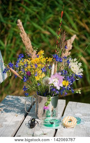 bouquet of wild flowers in a metal cup with floats