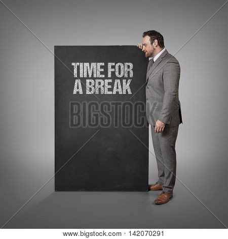 Time for a break text on blackboard with businessman standing side