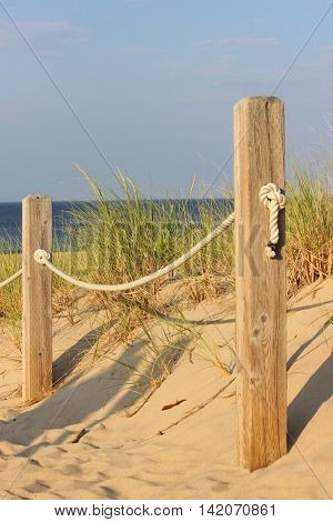 A fence at a beach in Cape Cod, Massachusetts on a sunny day in summer.