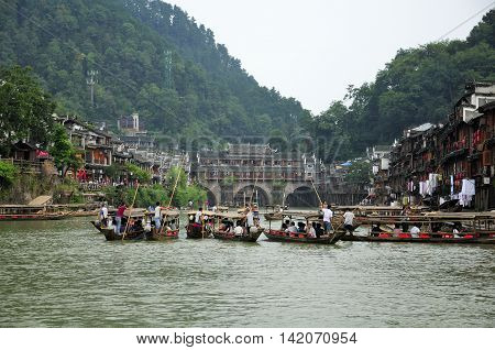 September 13 2015. Fenghuang China. The famous landmark Hongqiao and chinese boats on the Tuo Jiang River within Fenghuang Village in Hunan province China on an overcast day.