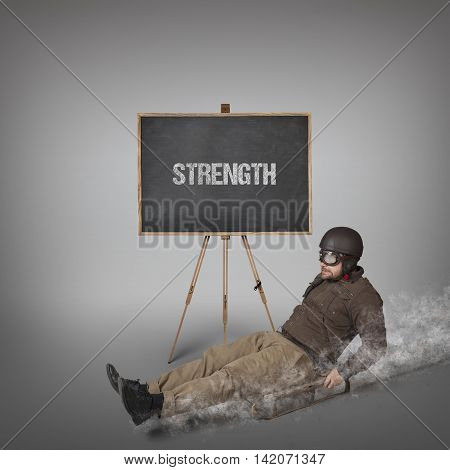 Strength text on blackboard with businessman sliding with a sledge