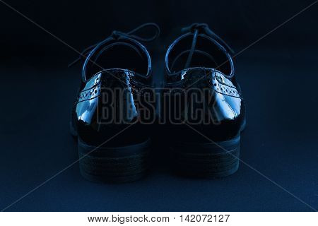 Footwear Concept. Horizontal Image. Pair of black female classic leather shoes on the black background. Selective focus. Blue colored