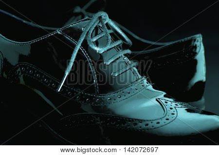 Footwear Concept. Horizontal Image. Pair of black female classic leather shoes on the black background. Selective focus. Blue colored.