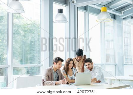 Multiethnic group of young business people creating presentation and using laptop together in office