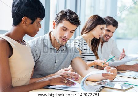 Group of serious young business people sitting and creating business plan in office