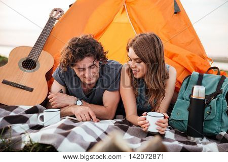 Happy young couple camping on the beach laying in the tent and reading book
