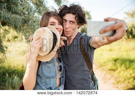 Young smiling happy cheerful couple w hiking in the forest and making selfie, making funny faces