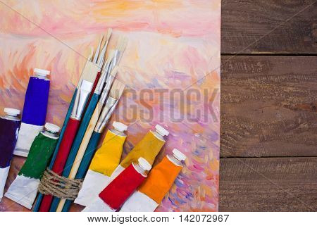Paints, brushes, palette and painted canvas. The workplace of the artist. Banner for the school.