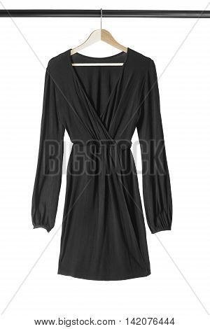 Black dress on wooden clothes rack isolated over white