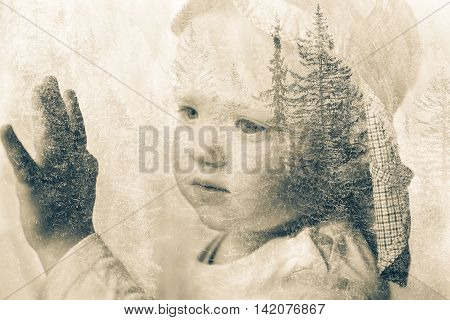 Little boy daydreaming looking out the window at nature thinking about it. Double exposure of child portrait and forest landscape. Hope dreaming back to nature future sustainability concept.