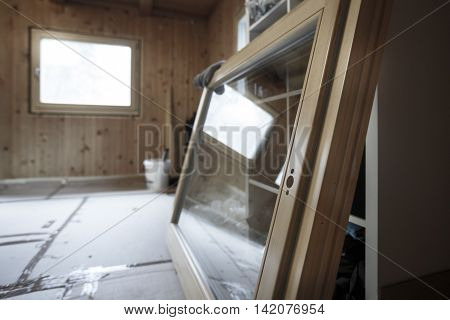 New efficient three pane wooden window prepared for installation in an old wooden house changing wasteful old windows. Home renovation sustainable living energy efficiency concept.