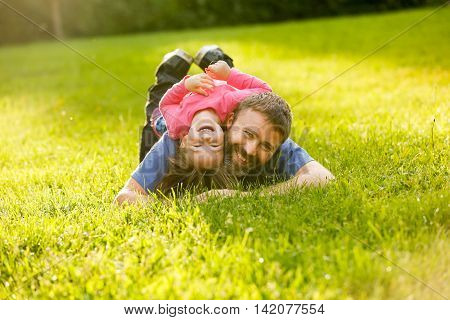 Devoted father and daughter lying on grass enjoying each others company bonding playing having fun in nature on a bright sunny day. Parenthood lifestyle childhood and family life concept.